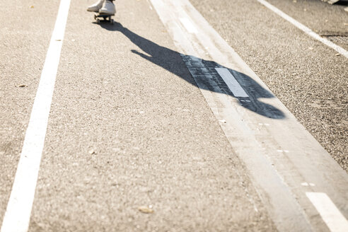 Shadow of man skateboarding on cycle path - VABF02080