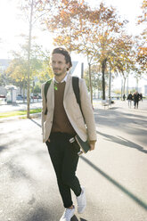Portrait of man with backpack and skateboard in the city in autumn - VABF02092