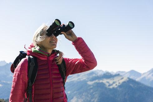 Austria, Tyrol, woman looking through binoculars during hiking trip - UUF16328