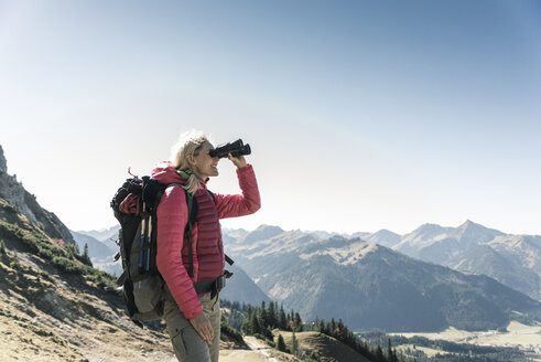 Austria, Tyrol, woman looking through binoculars during hiking trip - UUF16346