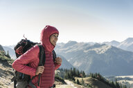 Austria, Tyrol, smiling woman on a hiking trip in the mountains enjoying the view - UUF16352