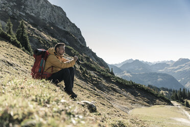 Austria, Tyrol, man having a break during a hiking trip in the mountains - UUF16355