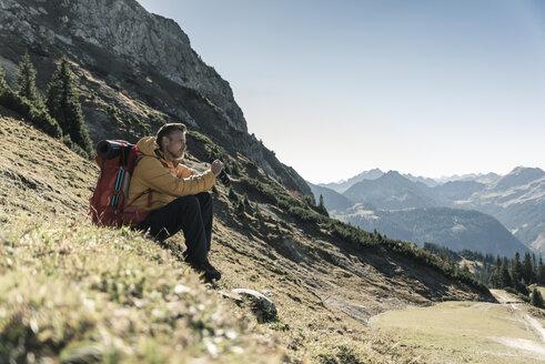Austria, Tyrol, man having a break during a hiking trip in the mountains - UUF16355
