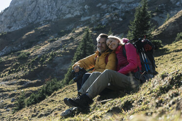 Austria, Tyrol, couple having a break during a hiking trip in the mountains - UUF16358