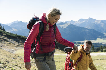 Austria, Tyrol, smiling couple hiking hand in hand in the mountains - UUF16364