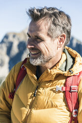 Austria, Tyrol, portrait of smiling man on a hiking trip in the mountains - UUF16373