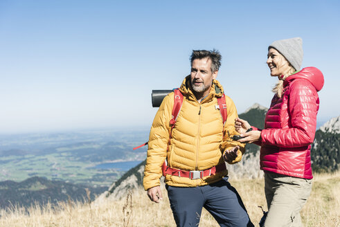 Austria, Tyrol, couple with compass hiking in the mountains - UUF16391