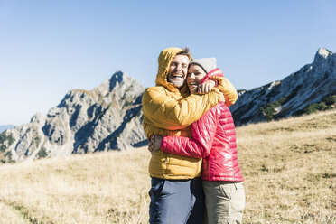 Austria, Tyrol, happy couple hugging on a hiking trip in the mountains - UUF16394