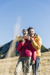 Austria, Tyrol, happy couple embracing on a hiking trip in the mountains - UUF16397