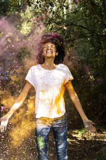 Woman standing in cloud of colorful powder paint, celebtaing Holi festival - ERRF00459