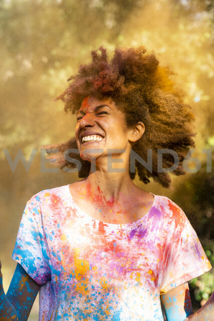 Woman shaking her head, full of colorful powder paint, celebrating Holi, Festival of Colors - ERRF00471