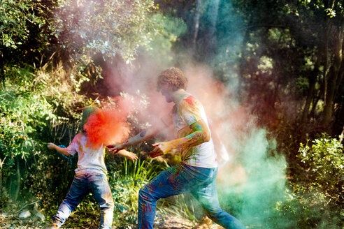 happy family celebrating Holi festival in the forest, throwing colorful powder paint - ERRF00501