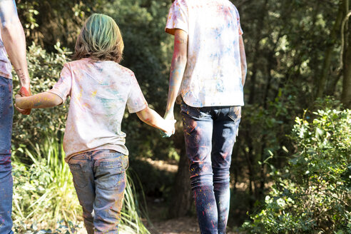 Family in the forest, full of colorful powder paing, after celebrating Holi, Festival of colors - ERRF00507