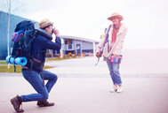 Backpacker couple taking photograph at airport - CUF46569