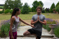 Female yoga teacher teaching young man yoga in garden, tree pose - CUF46587