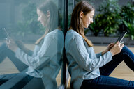 Woman leaning on glass wall using digital tablet - CUF46632