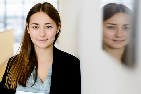 Businesswoman and her mirror reflection on wall - CUF46638
