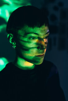 Woman daydreaming, green light reflected on face - CUF46671