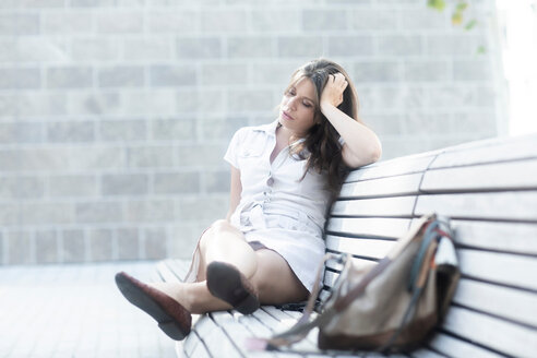 Woman on bench looking tired - CUF46713