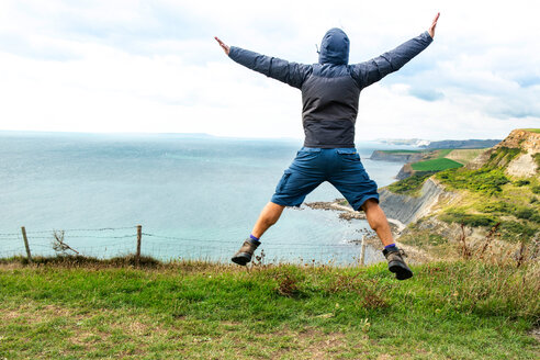 Man jumping on clifftop by sea, Bournemouth, UK - CUF46725