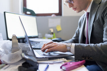Man using laptop and desktop in office - CUF46734