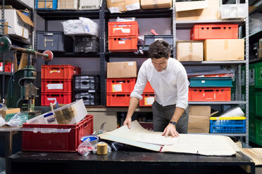 Man working on charts and plans in warehouse - CUF46740