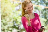 Young woman using smartphone in park - CUF46890