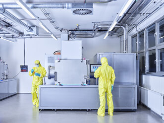 Chemists working in industrial laboratory, wearing protective clothing in the clean room - CVF01091