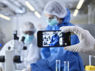 Hand holding smartphone, photographing chemists,  working in industrial laboratory - CVF01109