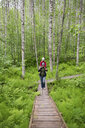 Finland, Kuopio, mother and daughter walking in a birch forest - PSIF00207