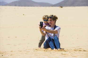 Spain, Canary Islands, Fuerteventura, Parque Natural de Corralejo, mother and daughter taking a selfie in sand dunes - RUNF00864
