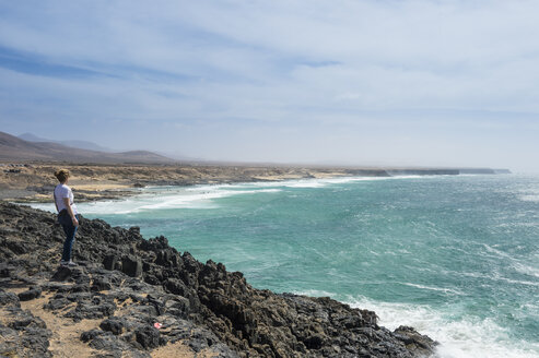 Spain, Canary Islands, Fuerteventura, woman looking at El Cotillo beach - RUNF00870