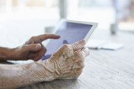 Woman's hand holding digital tablet, close-up - RBF06988