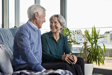Laughing senior couple sitting together on couch - RBF06991