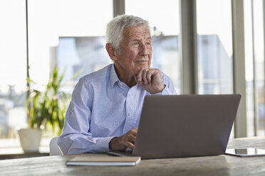 Portrait of pensive senior man sitting at table with laptop looking at distance - RBF07003