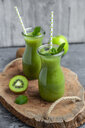 Two glass bottles of apple kiwifruit smoothie - SARF04048