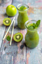 Two glass bottles of apple kiwifruit smoothie - SARF04051