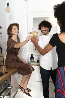 Friends having fun at a party, drinking wine in the kitchen - ERRF00544