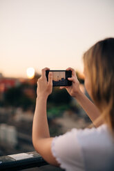 Cropped image of young woman photographing Fernsehturm through smart phone during sunset - MASF10316