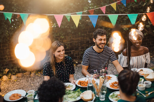 Happy multi-ethnic friends enjoying dinner at table during garden party - MASF10409