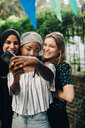 Happy multi-ethnic female friends taking selfie through mobile phone in backyard - MASF10505
