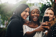 Smiling multi-ethnic female friends taking selfie through mobile phone in backyard - MASF10508