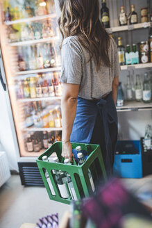 Female employee carrying bottles in crate at deli - MASF10565