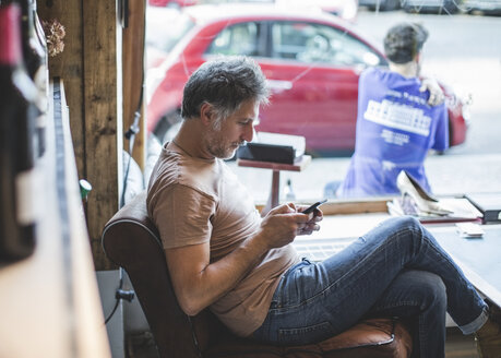 Mature owner using mobile phone while sitting on chair in deli - MASF10583