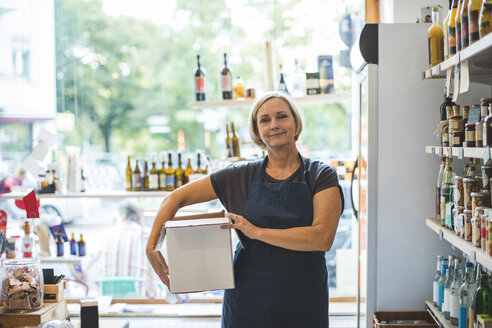 Portrait of confident female owner carrying cardboard box in deli - MASF10586