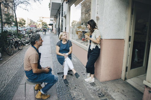 Male and female upholstery workers talking at sidewalk outside workshop - MASF10604