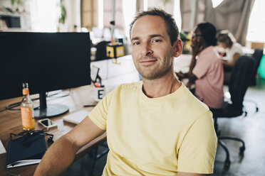 Portrait of confident businessman sitting in creative office - MASF10670