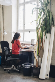 Side view of businesswoman using laptop at desk in creative office - MASF10757