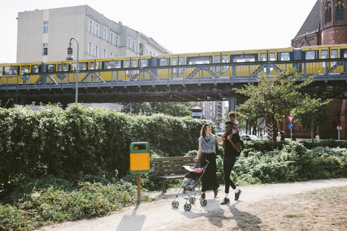 Young man carrying daughter on shoulders while woman pushing baby stroller at footpath against railway bridge - MASF10766