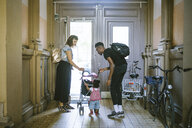 Mother and father looking at daughter pushing baby stroller in corridor of apartment - MASF10775